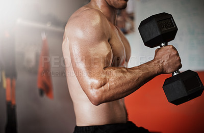 Buy stock photo Cropped shot of an unrecognizable muscular young man working out with a dumbbell in the gym