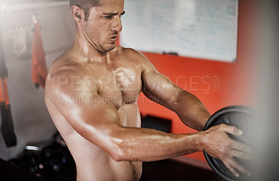 Buy stock photo Cropped shot of a handsome and muscular young man working out with a weight in the gym