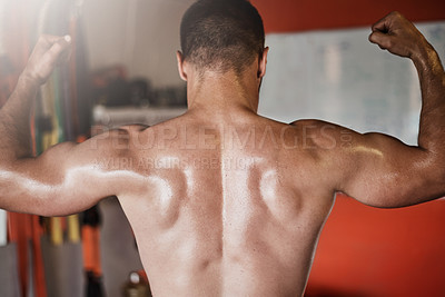 Buy stock photo Rearview shot of an unrecognizable muscular young man showing off his biceps in the gym
