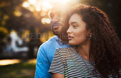 Buy stock photo Cropped shot of a young attractive couple spending time together outside in a public park