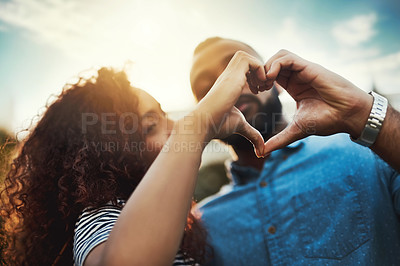 Buy stock photo Cropped shot of a young attractive couple making a heart frame with their hands outside in a public park