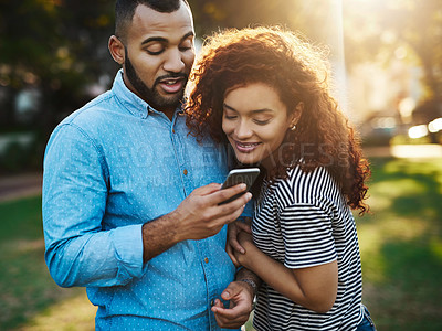 Buy stock photo Shot of a happy couple using a mobile phone together in the park