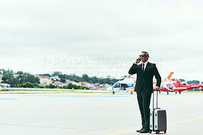 Buy stock photo Full length shot of a handsome mature businessman walking with his luggage outside of the airport