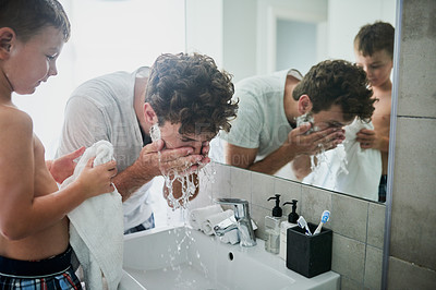 Buy stock photo Shot of a little boy watching his father rinse his face while shaving in the bathroom at home