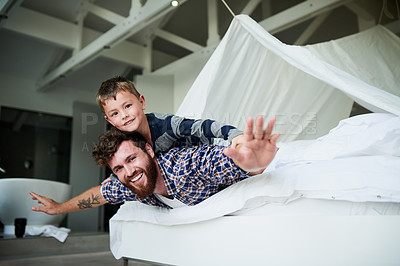 Buy stock photo Cropped portrait of a handsome young man lying on the bed at home with his arms spread out and his son on his back