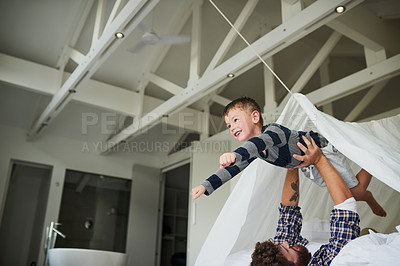 Buy stock photo Cropped shot of a young man holding his son up like a superhero while playing on the bed