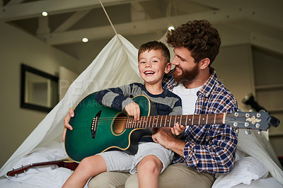 Buy stock photo Cropped portrait of an adorable little boy sitting on his dad's lap while learning to play the guitar at home