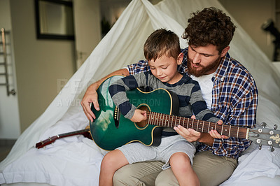 Buy stock photo Cropped shot of an adorable little boy sitting on his dad's lap while learning to play the guitar at home