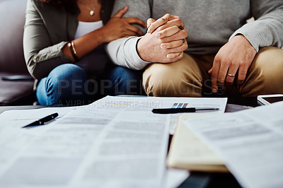 Buy stock photo Shot of an unrecognizable couple holding hands while going paperwork together at home