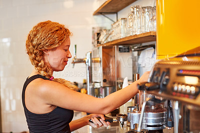 Buy stock photo Shot of a female barista on duty in a coffee shop