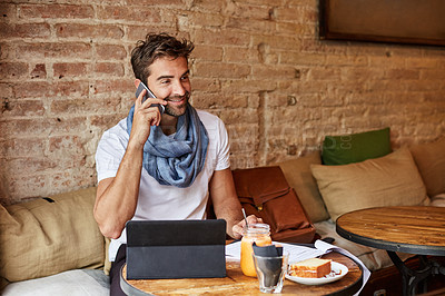 Buy stock photo Shot of a handsome young man using his digital tablet while sitting in a cafe