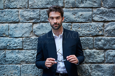 Buy stock photo Shot of a handsome young businessman in an urban alleyway