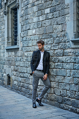 Buy stock photo Full length shot of a handsome young businessman standing against a brick wall in an urban alleyway