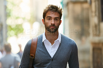Buy stock photo Cropped portrait of a handsome young businessman walking through an urban alleyway on a sunny day