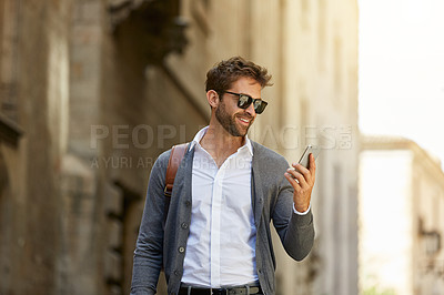 Buy stock photo Cropped shot of a handsome young businessman checking his messages while walking through an urban alleyway