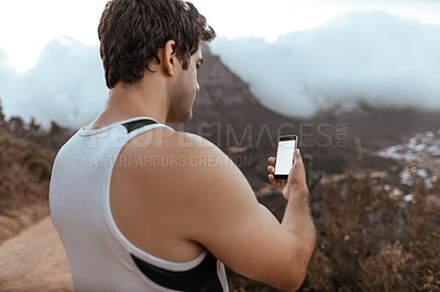 Buy stock photo Rearview shot of a handsome young man checking his cellphone while running in the mountains