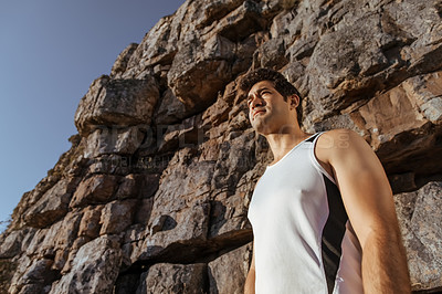 Buy stock photo Low angle shot of a handsome young man taking in the views while running in the mountains