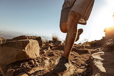 Buy stock photo Low angle shot of an unrecognizable young man out for a run in the mountains