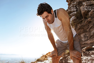 Buy stock photo Low angle shot of a handsome young man looking tired while out for a run in the mountains