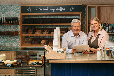 Buy stock photo Cropped portrait of a mature couple working on a tablet while standing behind the counter of their self-owned coffee shop