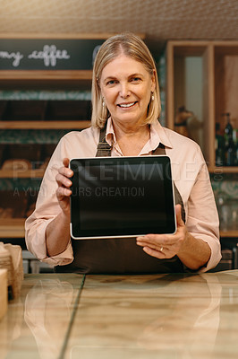 Buy stock photo Cropped portrait of a mature female entrepreneur showing you a tablet screen while standing in her self-owned coffee shop