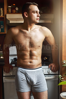 Buy stock photo Cropped shot of a handsome young shirtless man in the kitchen at home