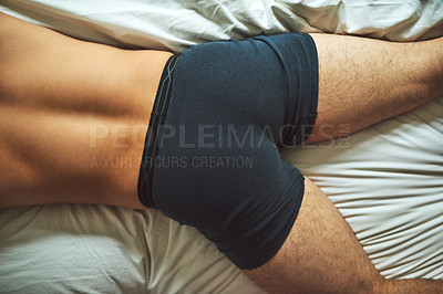 Buy stock photo High angle shot of an unrecognizable shirtless man lying on his bed at home
