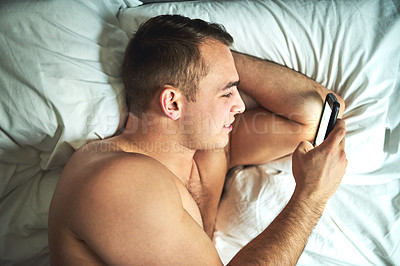 Buy stock photo Cropped shot of a young handsome shirtless man using a cellphone in bed at home