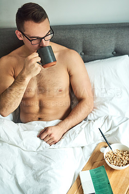 Buy stock photo Cropped shot of a handsome young shirtless man drinking coffee and having breakfast in bed at home