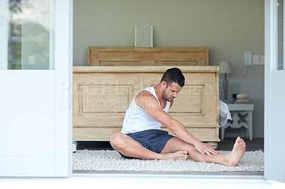Buy stock photo Shot of a young handsome man stretching at home