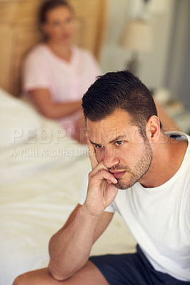 Buy stock photo Cropped shot of a married couple having a disagreement in the bedroom at home