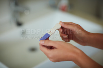 Buy stock photo Cropped shot of an unrecognizable woman holding a pregnancy test in the bathroom at home