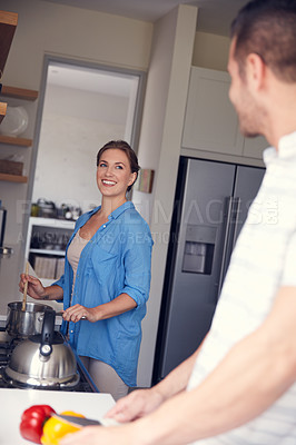 Buy stock photo Cropped shot of a married couple making food together in the kitchen at home