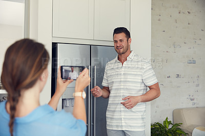 Buy stock photo Cropped shot of an unrecognizable woman taking a picture of her husband in the kitchen at home