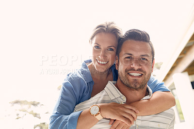 Buy stock photo Cropped shot of a young handsome man giving his beautiful wife a piggyback ride outside