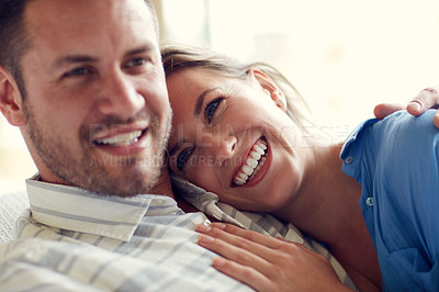 Buy stock photo Cropped shot of a young attractive wife lying on her husband's chest in the living room at home
