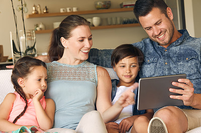 Buy stock photo Shot of a family of four sharing a digital tablet