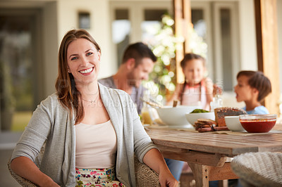 Buy stock photo Defocused shot of a  woman at home with her family sitting in the background
