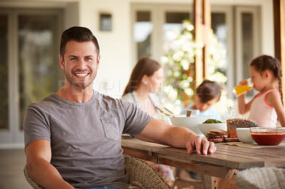 Buy stock photo Portrait of a man at home with his family sitting in the background