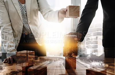 Buy stock photo Cropped shot of two unrecognisable businesspeople stacking wooden blocks together in an office superimposed over a city background