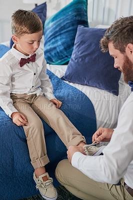 Buy stock photo Cropped shot of a young handsome father tying his son's shoelaces at home