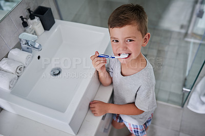 Buy stock photo Portrait of an adorable little boy brushing his teeth in the bathroom at home