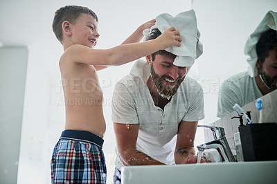 Buy stock photo Shot of a little boy wiping his father's head while shaving in the bathroom at home