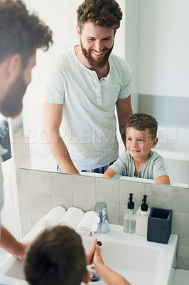 Buy stock photo Cropped shot of a young handsome father helping his adorable little boy wash his hands in the bathroom at home