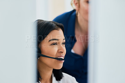 Buy stock photo Shot of two young women using a computer together in a call center