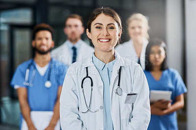 Buy stock photo Portrait of a young doctor standing in a hospital with her colleagues in the background