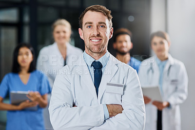 Buy stock photo Portrait of a young doctor standing in a hospital with his colleagues in the background