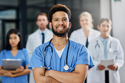 Buy stock photo Portrait of a young medical practitioner standing in a hospital with his colleagues in the background
