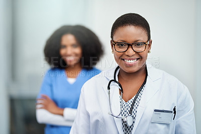 Buy stock photo Portrait of a young doctor standing in a hospital with her colleague in the background