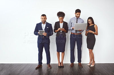 Buy stock photo Studio shot of a group of young businesspeople standing in line and using their wireless devices against a gray background